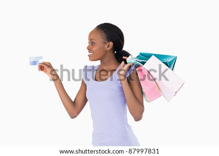 Smiling woman with her shopping and credit card on white background