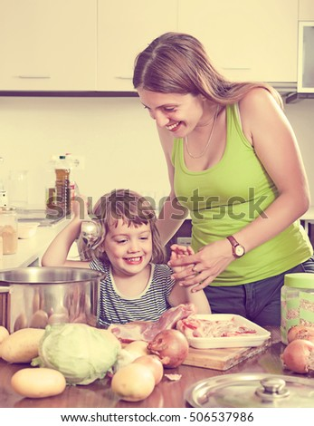 Smiling woman with little girl cooking together at home kitchen