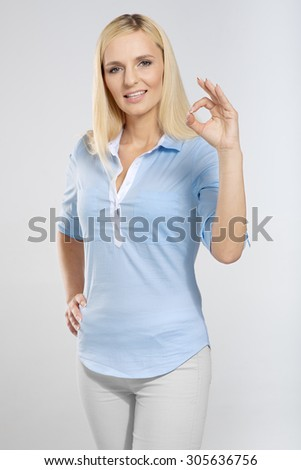 Smiling woman with okay gesture - stock photo