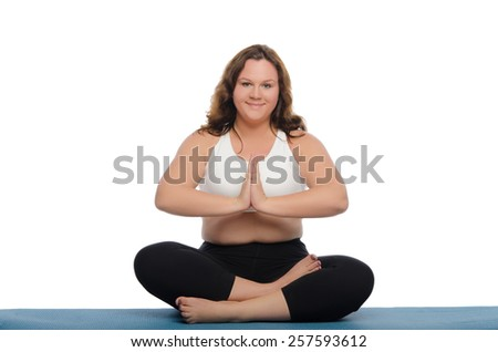 Smiling woman with overweight is meditating on blue mat - stock photo