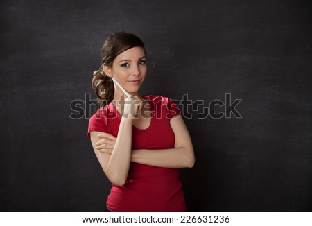 Smiling Woman with pen. Blackboard/chalkboard concept - stock photo