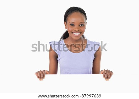 Smiling woman with placeholder in her hands on white background - stock photo