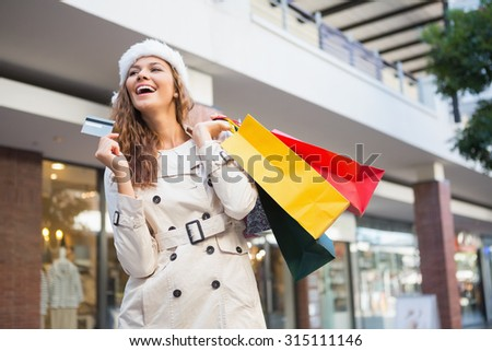 Smiling woman with shopping bags and credit card at the shopping mall - stock photo