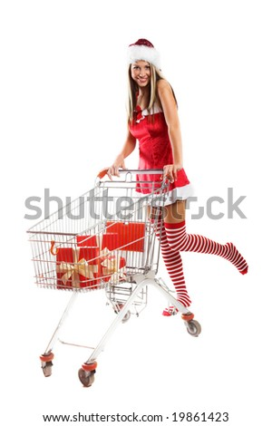 smiling woman with some christmas gifts and a shopping caddy - stock photo