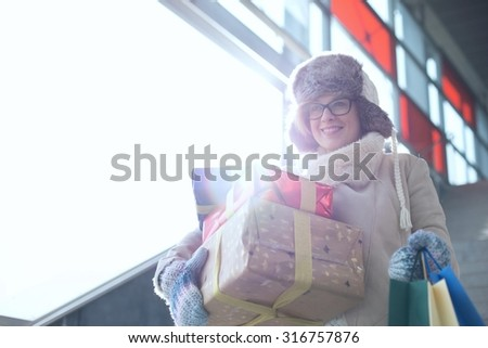 Smiling woman with stacked gifts and shopping standing by window during winter - stock photo