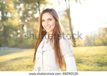 smiling woman with sunny autumn park in background