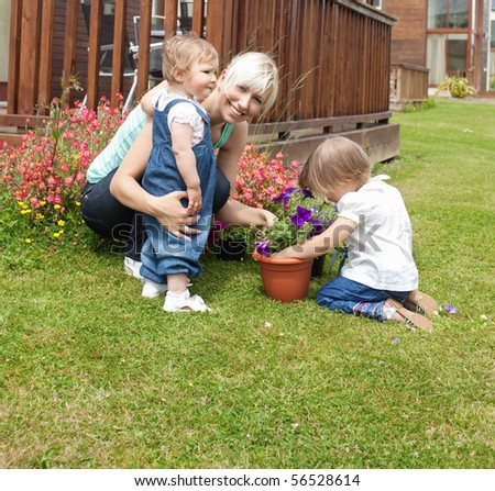 Smiling woman with two children in the garden plant flowers - stock photo