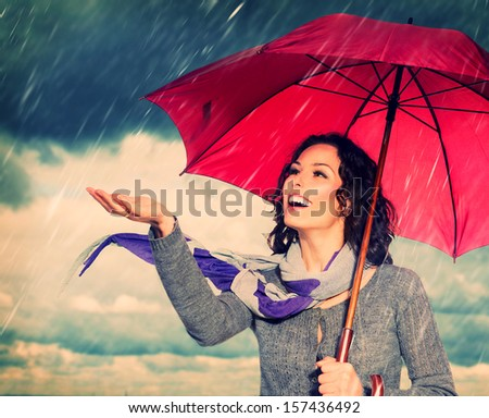 Smiling Woman with Umbrella over Autumn Rain Background. Laughing Healthy Girl outdoors. Bad Weather