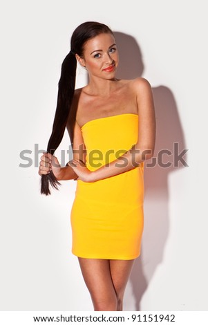 Smiling Woman With Very Long Brunette Hair in pony tail and strapless mini skirt posing on white studio bakground. - stock photo