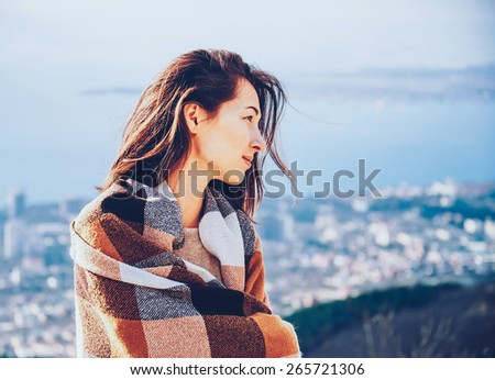 Smiling woman wrapped in plaid standing on background of the city in autumn. Image with instagram filter - stock photo