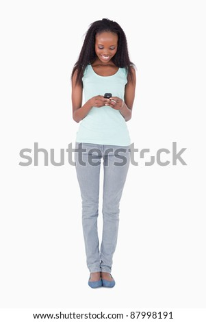 Smiling woman writing text message on white background - stock photo