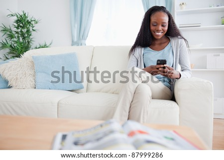 Smiling woman writing text message while sitting on sofa - stock photo