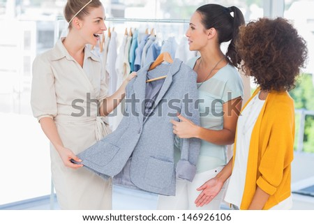 Smiling women holding a blazer in a creative office - stock photo