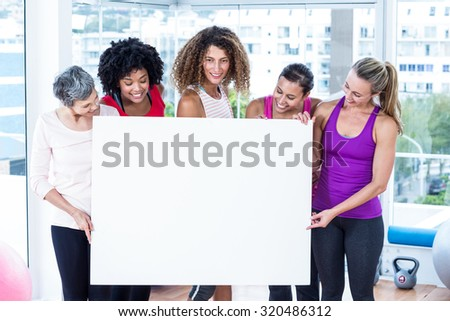 Smiling women holding board in fitness studio - stock photo