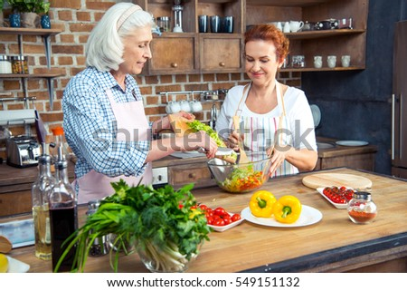 Smiling women in aprons cooking together in kitchen