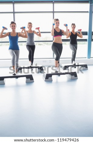Smiling women lifting weights while doing aerobics in gym - stock photo