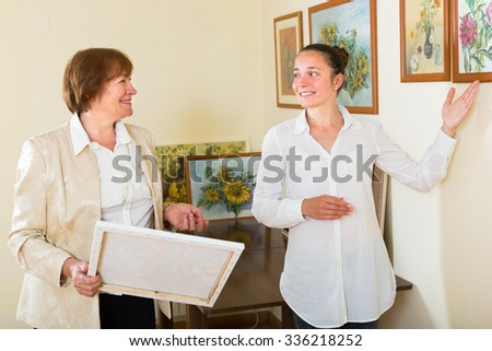 Smiling women looking at the creative picture in art gallery - stock photo