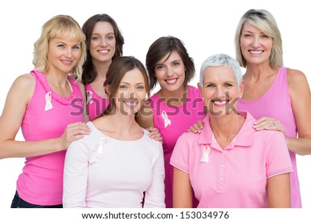 Smiling women posing and wearing pink for breast cancer on white background - stock photo