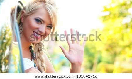 Smiling women wave goodbye - stock photo