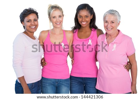 Smiling women wearing pink tops and breast cancer ribbons on white background - stock photo