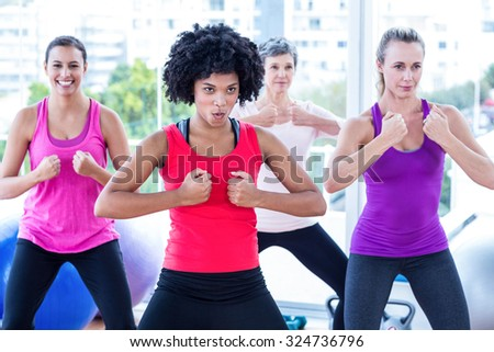 Smiling women with clasped hands in fitness studio - stock photo