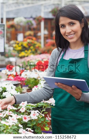 Smiling worker checking flowers in garden center with tablet computer - stock photo