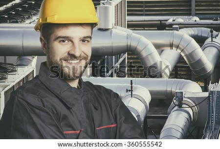 Smiling worker in protective uniform and protective helmet in front of industrial pipes - toned image,  retro film filtered in instagram style - stock photo
