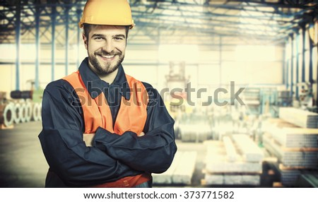 smiling worker in protective uniform and protective helmet in production hall - toned image, retro film filtered in instagram style - stock photo