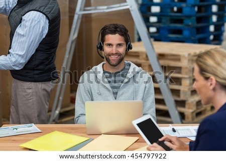 Smiling worker looking at camera while using a laptop