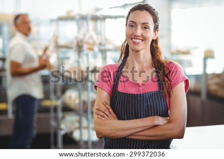 Smiling worker looking at camera with arm crossed in the bakery