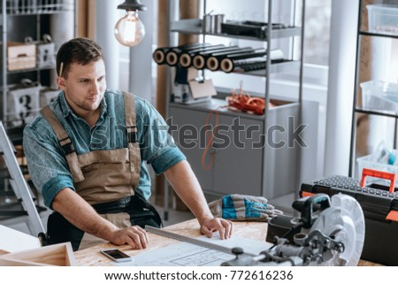 Smiling worker proud of his home renovation plan sitting at a wooden desk in his workshop