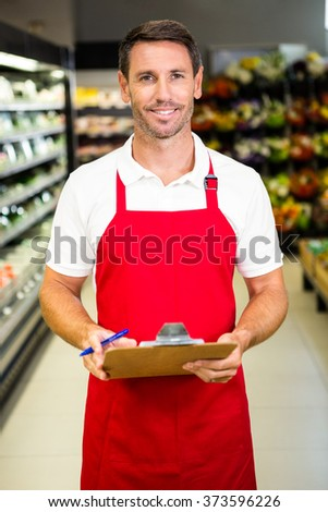 Smiling worker with clipboard in grocery store