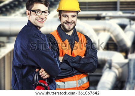 Smiling workers in protective uniform and protective helmet in front of industrial pipes - toned image, retro film filtered in instagram style - stock photo