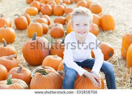 smiling 6-year old boy having fun and enjoying autumn time at pumpkin patch