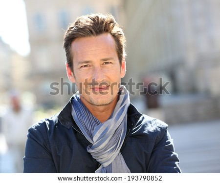 Smiling 40-year-old man in town - stock photo