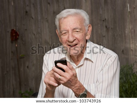 Smiling 90 year old senior old man on mobile smart phone - stock photo