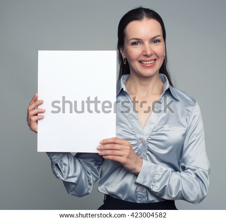 Smiling 30 year old woman holding blank card. Isolated on grey background - stock photo