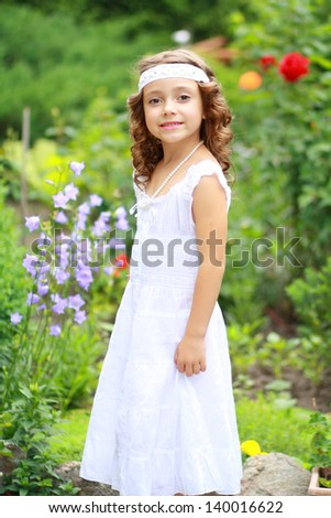 Smiling 6 years old girl in garden looking right at camera - stock photo