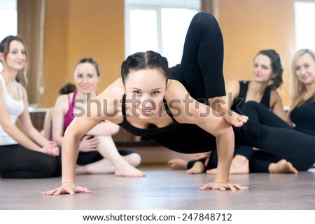 Smiling yogi girl exercising, doing handstand push-ups, group of friends watching on the background - stock photo