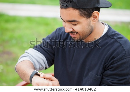Smiling young African American boy using his trendy smart watch sitting in a park on bench .Modern gadget that lets you always stay connected to internet,social media from everywhere - stock photo