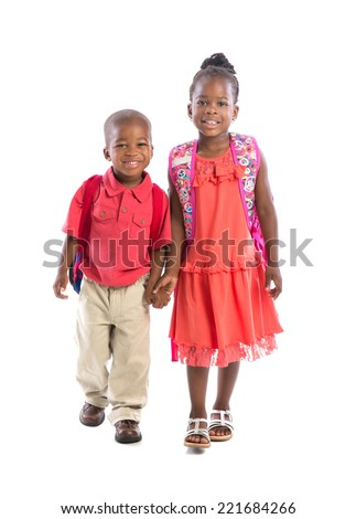 Smiling Young African American Brother and Sister Holding Hand Isolated on White Background Wearing Backpack Walking