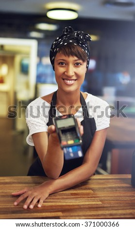 Smiling young African American female entrepreneur leaning on the wooden counter of her shop holding out a banking machine for a customer to process their card - stock photo