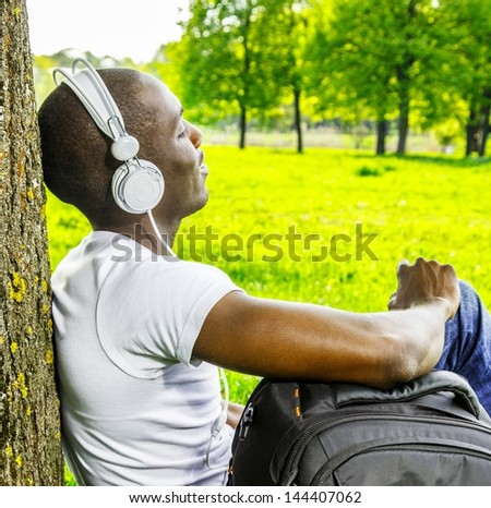 Smiling young african american man in white shirt listens music in a park - stock photo