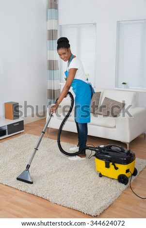 Smiling Young African Woman Cleaning Carpet With Vacuum Cleaner - stock photo