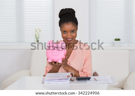 Smiling Young African Woman Holding Piggybank With Eyeglasses - stock photo