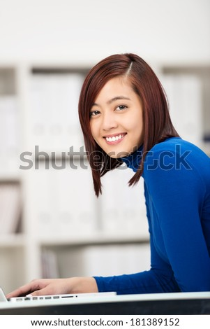 Smiling young Asian girl using a laptop computer sitting at a desk in the office or classroom looking sideways at the camera with a friendly smile - stock photo