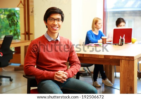 Smiling young asian student in classroom - stock photo