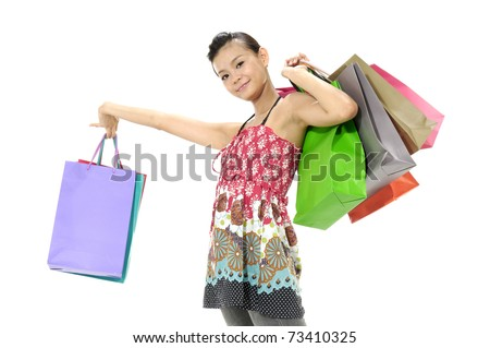 smiling young asian woman holding colorful shopping bags against white background