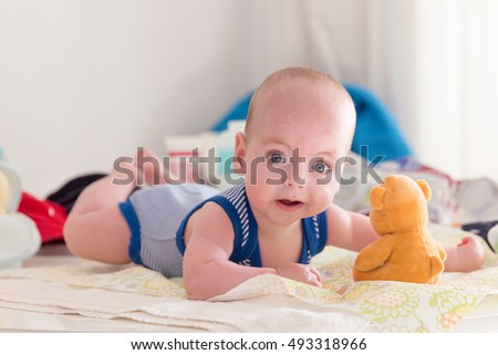 Smiling young baby boy with big blue eyes lying on his tummy with a teddy bear in front of him