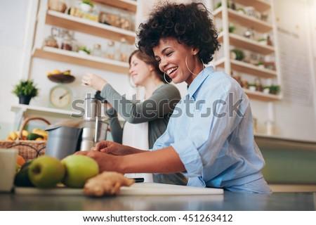 Smiling young bar employees standing behind bar counter preparing fresh fruit juice. - stock photo